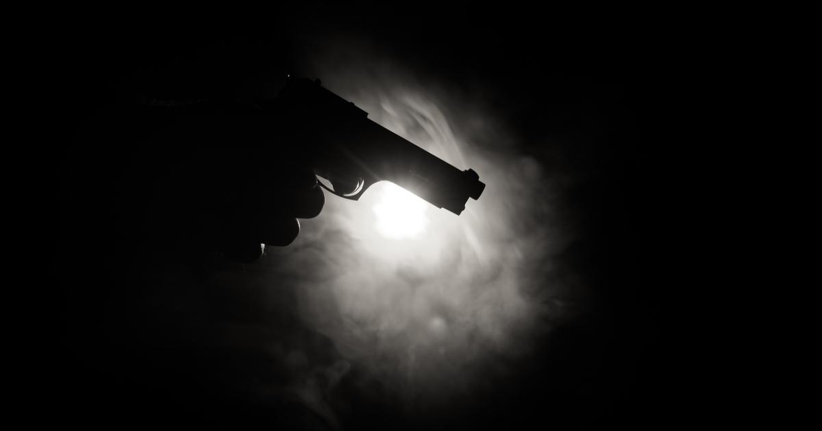 hand holding gun in the dark